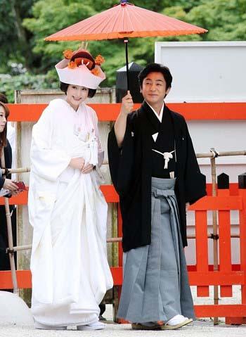 上賀茂神社で挙式をした片岡愛之助と藤原紀香が相合傘で参道を歩く姿