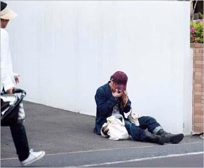 路上に座り込み、鼻をかんでいる草彅剛